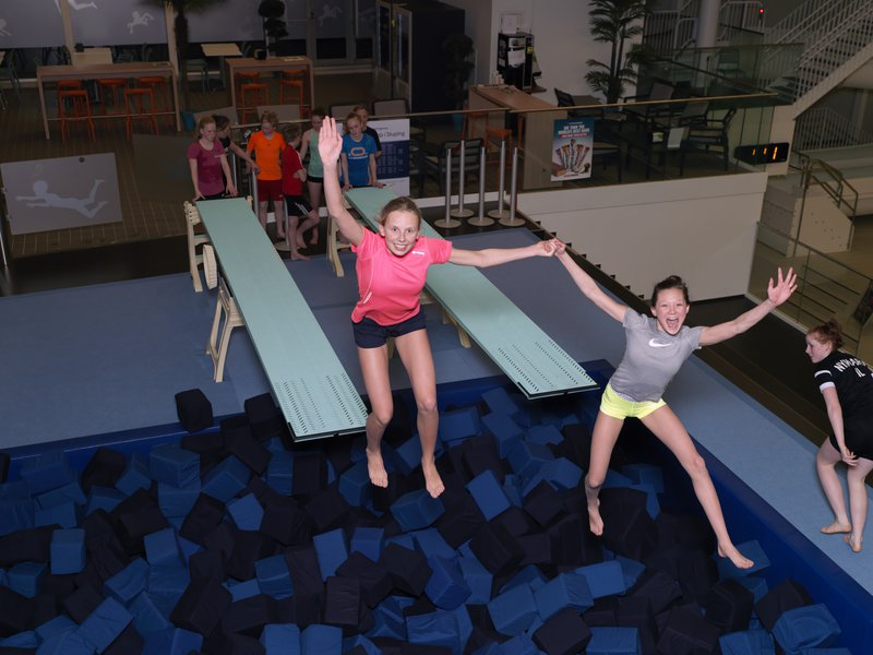 Children jumping from diving boards in the dry training area at AdO arena.